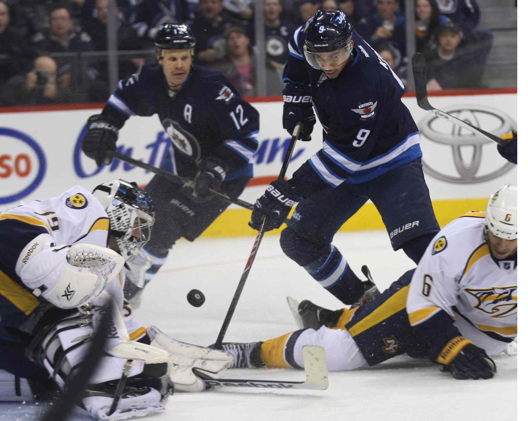 Evander Kane (9) chases the puck in front of Nashville Predators goaltender Marek Mazanec during the second period as Olli Jokinen (12) looks on.