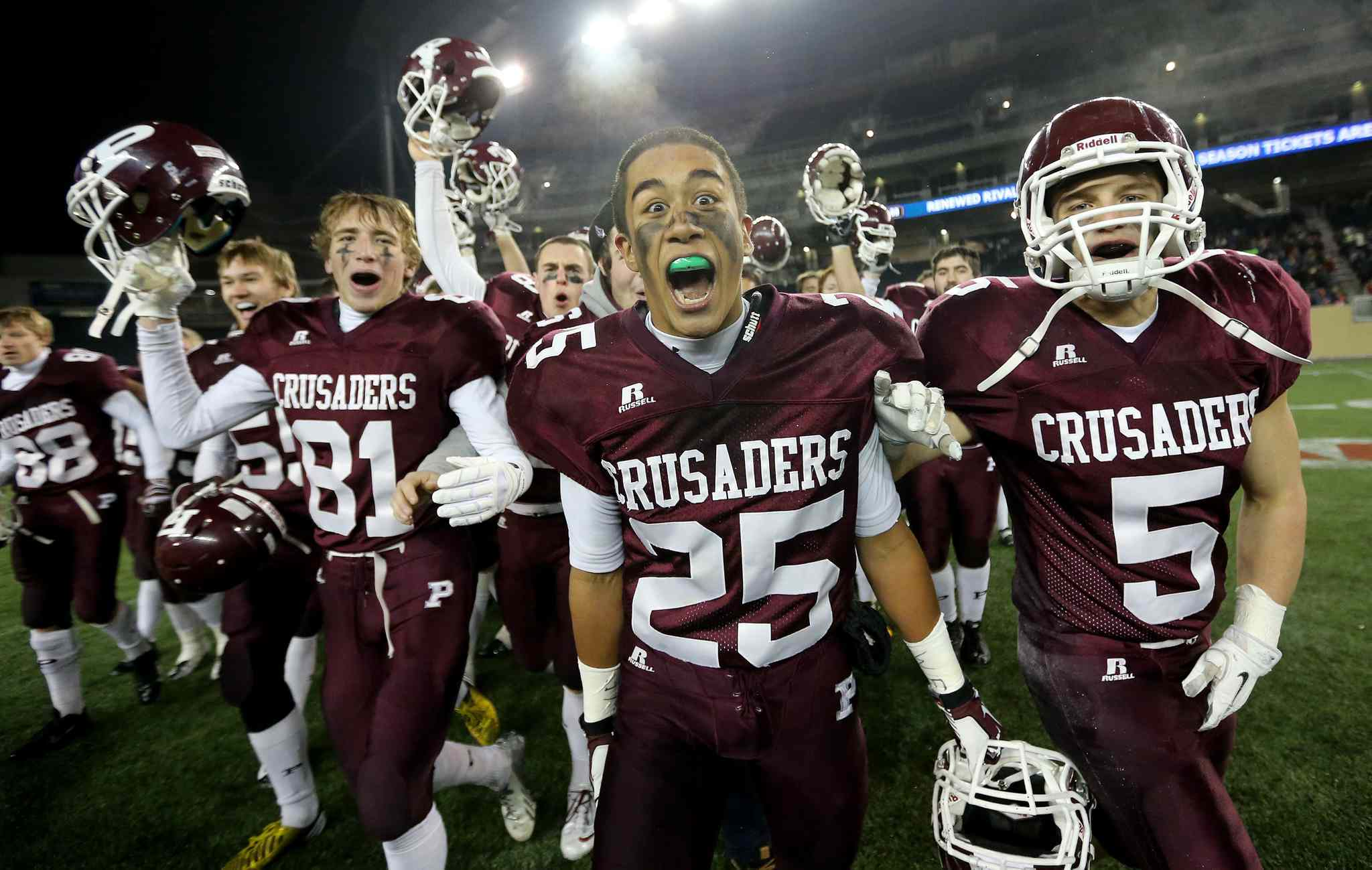 Matt MacDonald (81), Cody Cranston (25) and Teagan Horton (5) of the St. Paul's Crusaders celebrate their Anavets Bowl victory.