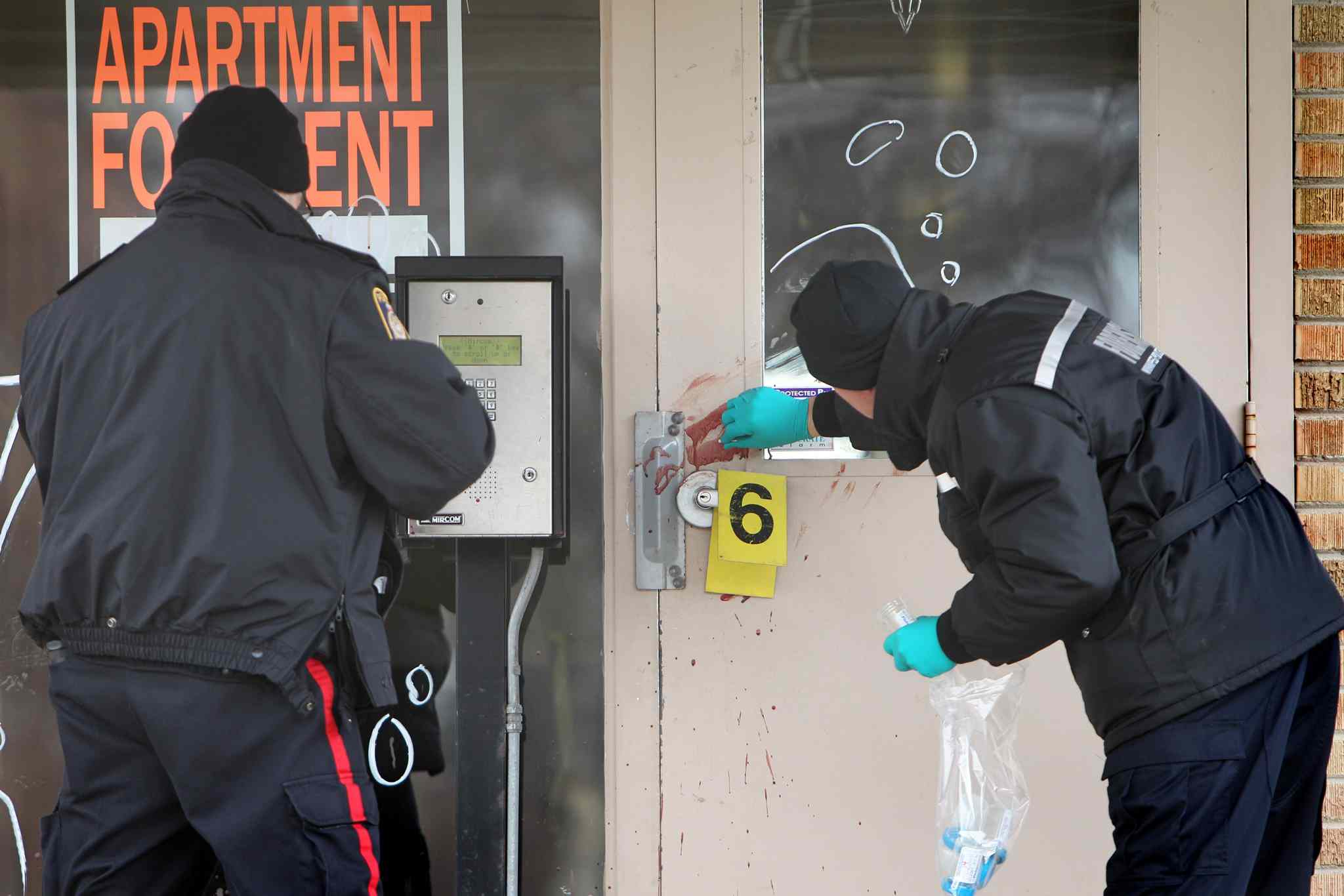 Police investigators examine the blood left behind at the Capri apartment building at 2130 Portage Ave. where they found three people suffering from various injuries Friday night. Two of the victims, a 42-year-old male and a 32-year-old female, were taken to hospital in stable condition. A third victim, a 39-year-old male, suffered upper body injuries and was taken to hospital in critical condition. He later died as a result of those injuries. RUTH BONNEVILLE / WINNIPEG FREE PRESS