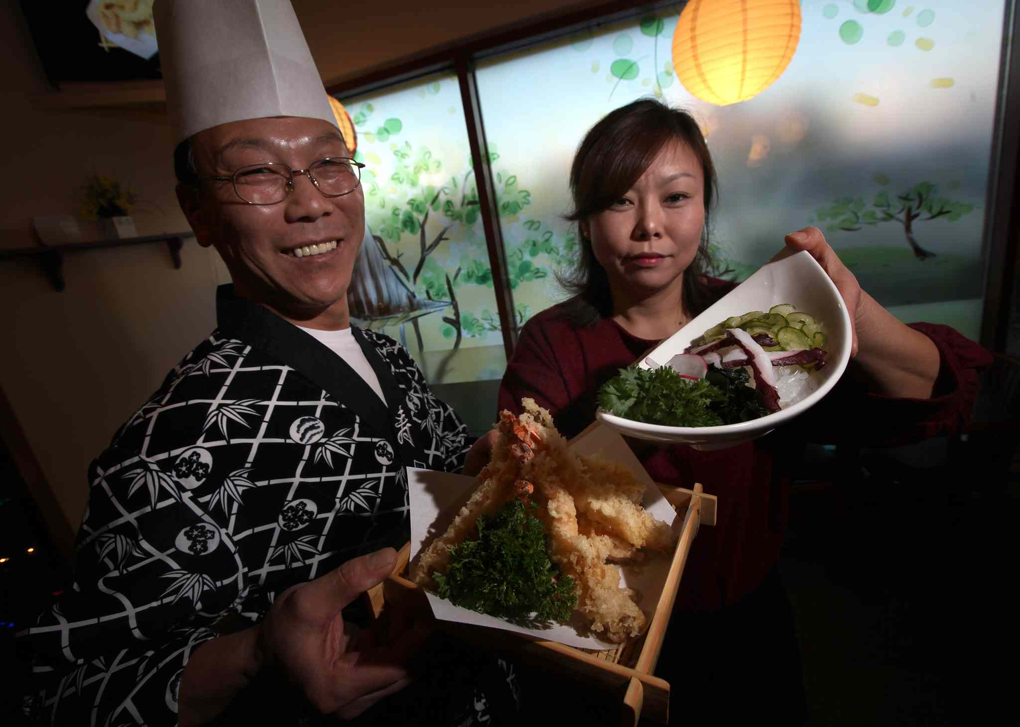 Chef Doeyeong Kang (left) and his wife Hyunhee Park with shrimp tempura and sunomono salad.