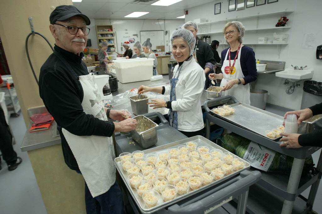 Volunteers Joe Everton and Janice Johnson prepare coleslaw in Siloam Mission's kitchen for the mission's Christmas Eve dinner Tuesday.