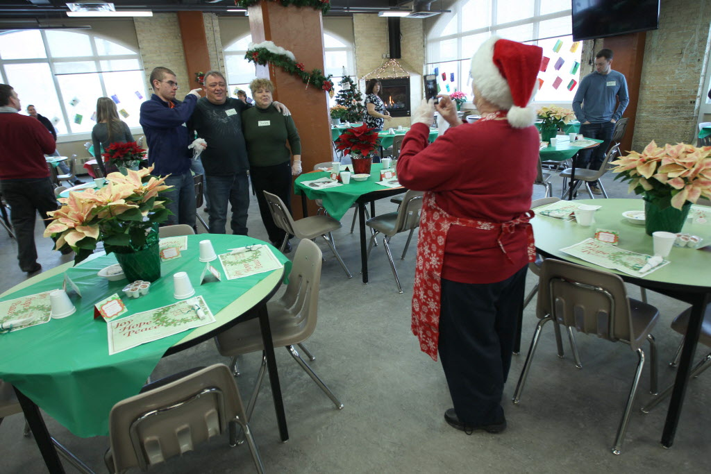 Before guests arrive for Christmas Eve dinner Tuesday, Siloam Mission volunteers take photos to commemorate the day.