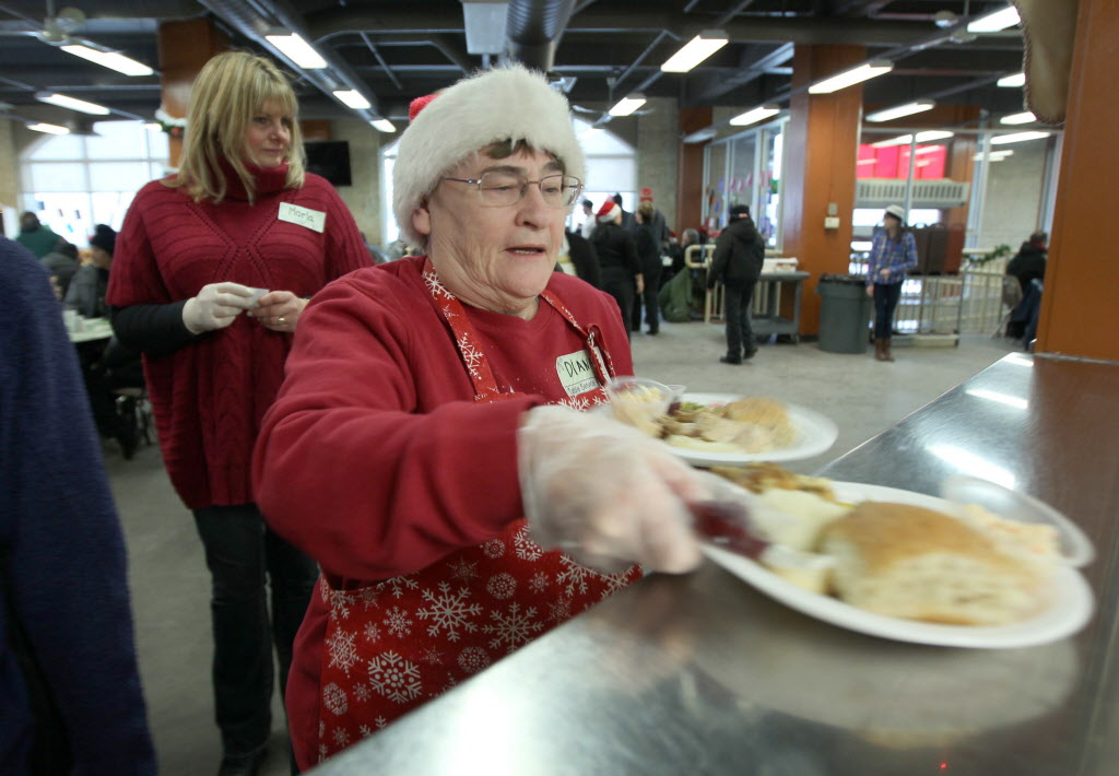 Volunteer Dianna Proctor serves up the turkey at Siloam Mission's Christmas Eve dinner Tuesday.