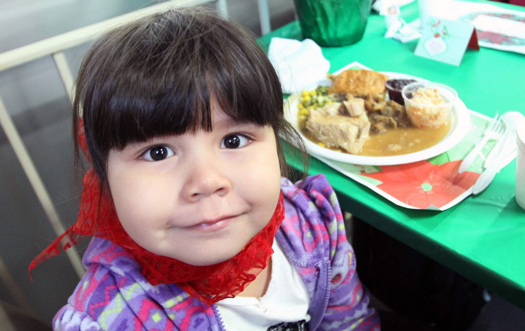 Four-year-old Mona Miracle enjoys Christmas Eve dinner at the Siloam Mission Tuesday afternoon.  (JOE BRYKSA / WINNIPEG FREE PRESS)