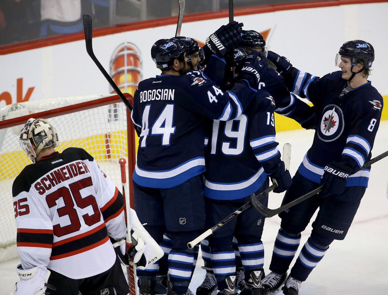 The Jets celebrate a third period goal by Andrew Ladd as Cory Schneider looks on.