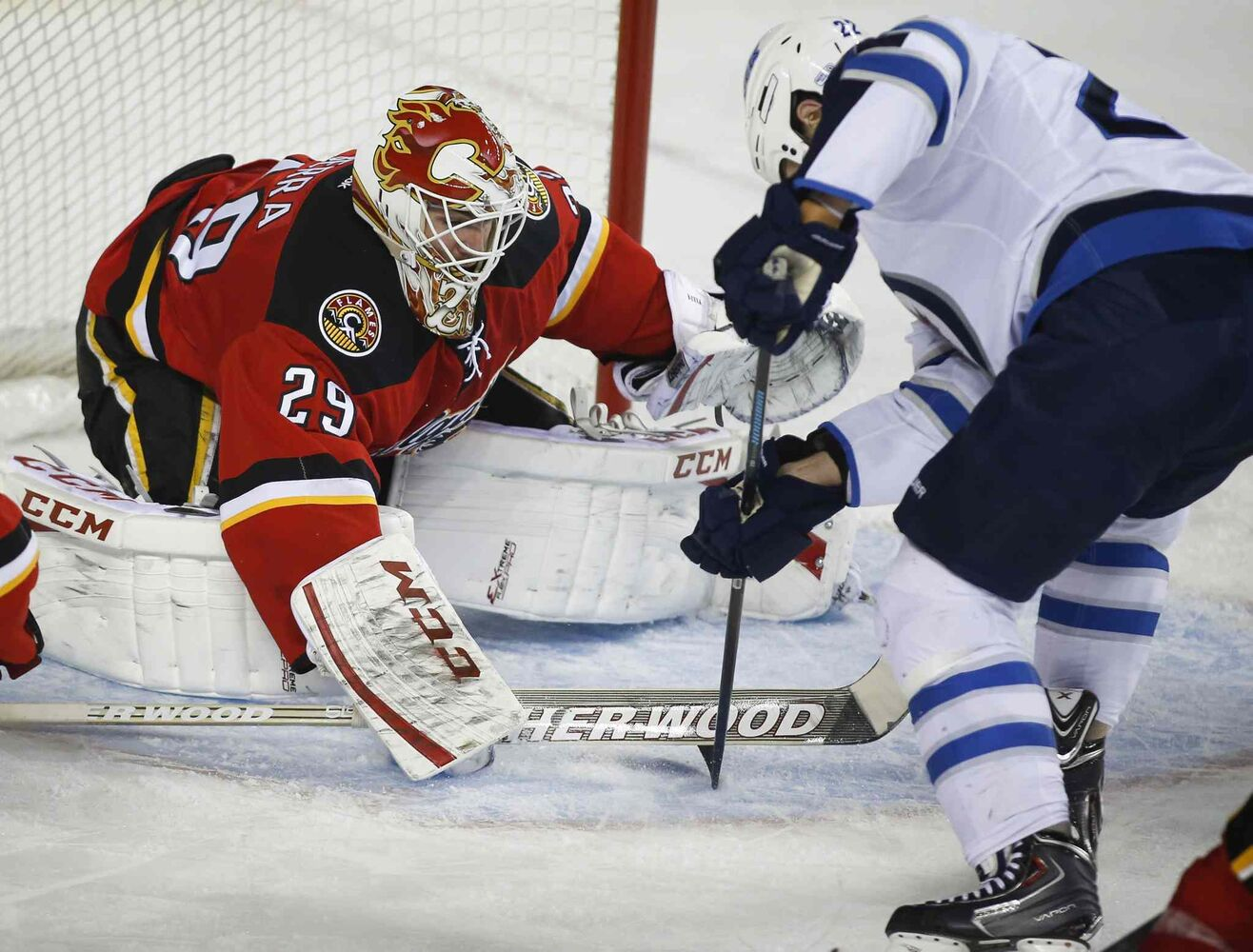 Winnipeg Jets' Chris Thorburn, right, has his stick trapped by Calgary Flames' goalie Reto Berra during the second period Thursday.  (Jeff McIntosh / The Canadian Press)