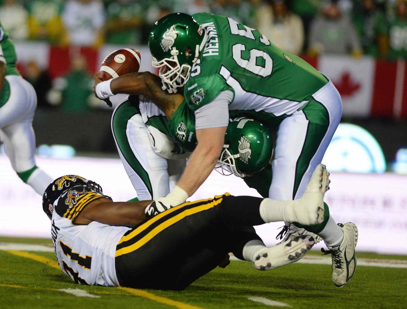 Saskatchewan Roughriders quarterback Darian Durant loses the ball as he is tackled by Hamilton Tiger-Cats defensive lineman Brandon Boudreaux while Roughriders offensive lineman Ben Heenan covers during the first quarter.