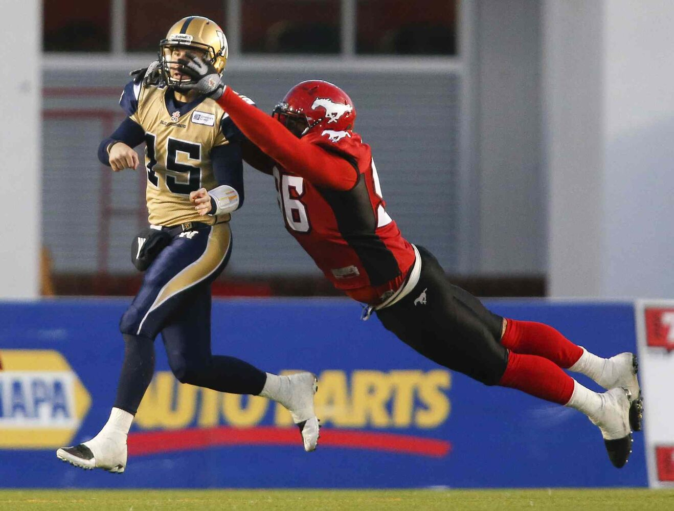 Winnipeg Blue Bombers quarterback Max Hall is tackled by Calgary Stampeders' Demonte Bolden during the second half. (Jeff McIntosh / The Canadian Press)