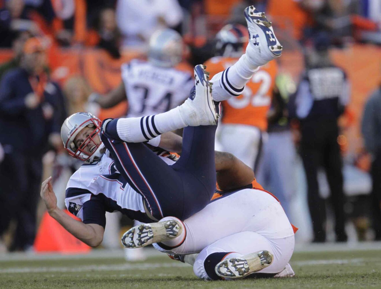 Patriots QB Tom Brady is sacked by Broncos defensive tackle Terrance Knighton. (Joe Mahoney / The Associated Press)