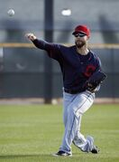 Cleveland Indians' Corey Kluber warms up during a spring training baseball practice, Sunday, Feb. 22, 2015, in Goodyear, Ariz. (AP Photo/John Locher)