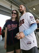 Michelle Romon of Fargo N.D., poses for a photo with Minnesota Twins pitcher Glen Perkins, right, as Perkins and other players greet fans at the front gate during a Twins open house event at baseball spring training in Fort Myers Fla., Sunday Feb. 22, 2015. Spring training is big business, just like the regular season, and the Twins have completed a $48.5 million renovation of their facility in southwest Florida, three years after their cross-town competitors the Boston Red Sox unveiled a luxurious new compound. (AP Photo/Tony Gutierrez)