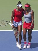 Venus, left, and Serena Williams walk to mid court after losing a quarterfinals doubles match to Ekaterina Makarova and Elena Vesnina, of Russia, during the 2014 U.S. Open tennis tournament, Tuesday, Sept. 2, 2014, in New York. (AP Photo/John Minchillo)