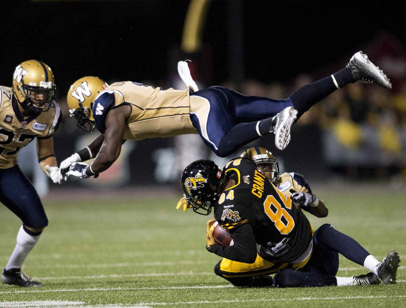 Winnipeg Blue Bombers' linebacker Ejiro Kuale leaps over Hamilton Tiger-Cats' receiver Bakan Grant, bottom right, during the second half of Thursday's game. (Nathan Denette / The Canadian Press)