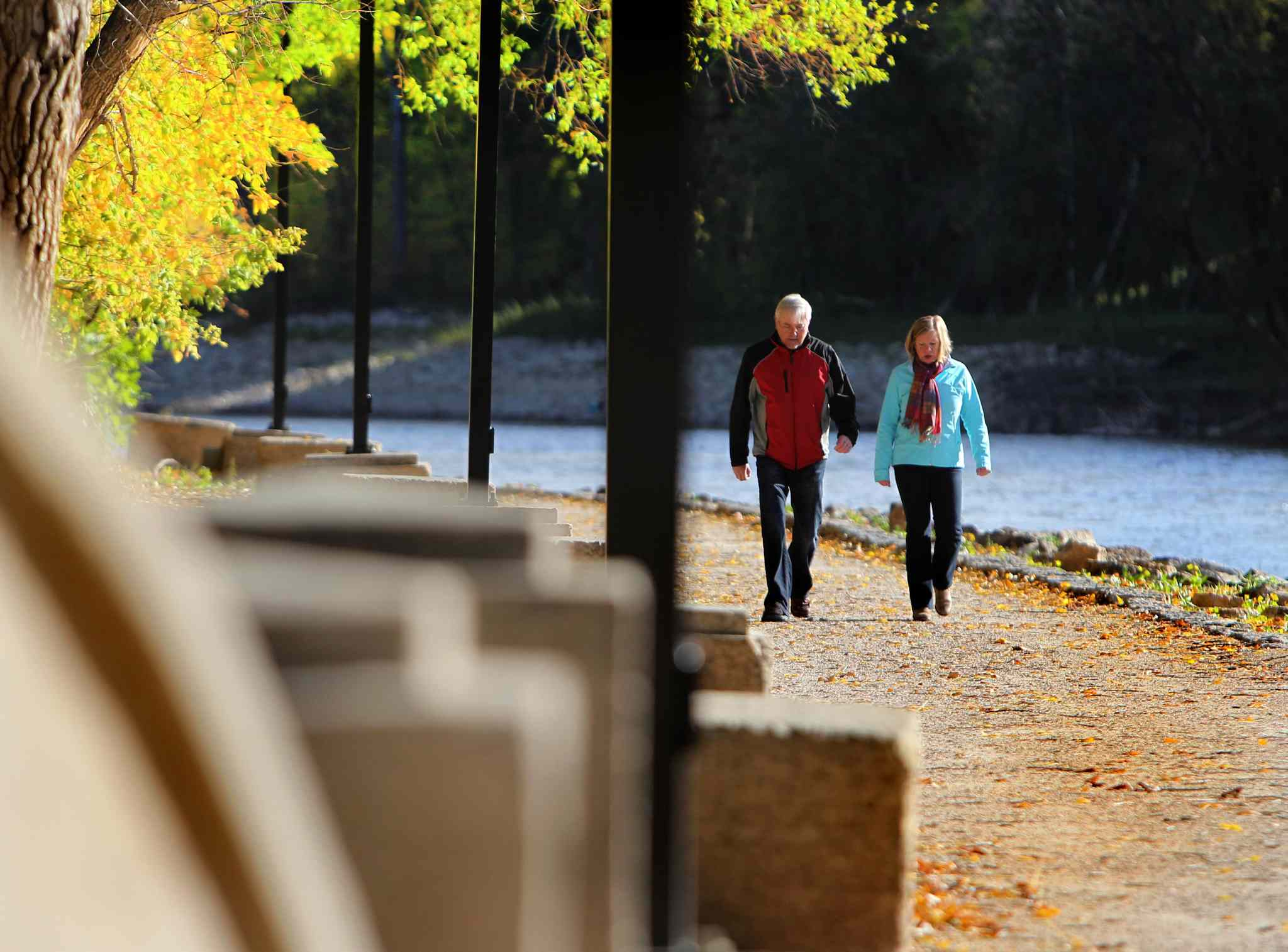A couple enjoys a brisk walk along the Assiniboine River Saturday morning under sunny skies.