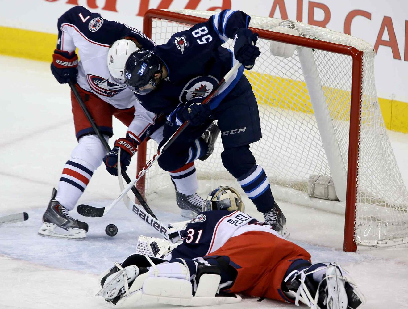 Columbus Blue Jackets' Jack Johnson (7) battles with Winnipeg Jets' Eric O'Dell (58) in the crease behind goaltender Curtis McElhinney (31). Then, O'Dell manages to put the puck in the net for his first career NHL goal during first period Saturday. (Trevor Hagan / Winnipeg Free Press)
