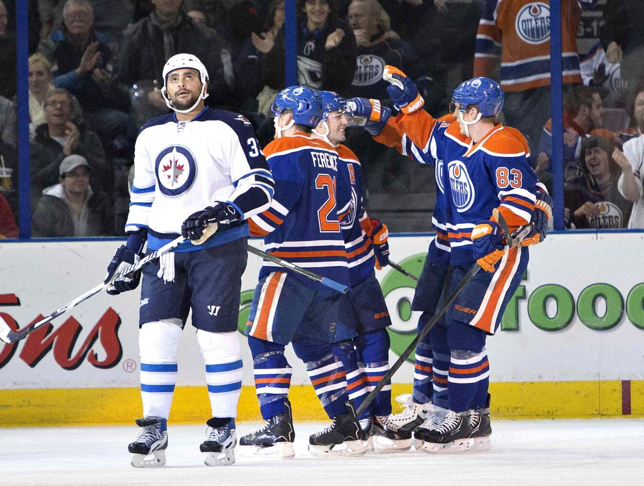 Winnipeg Jets' Dustin Byfuglien (33) looks on as Edmonton Oilers' Andrew Ference (21), Jordan Eberle (14) and Ales Hemsky (83) celebrate a goal during first period NHL hockey action in Edmonton on Monday. (Jason Franson / The Canadian Press)