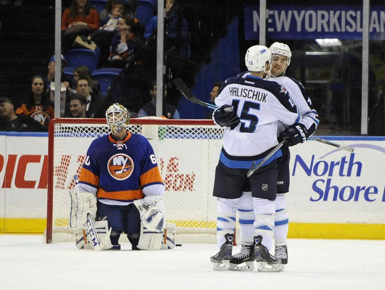 New York Islanders goalie Kevin Poulin (left) reacts as Winnipeg Jets forward Devin Setoguchi (right) celebrates his goal with Matt Halischuk in the second period. (Kathy Kmonicek / The Associated Press)