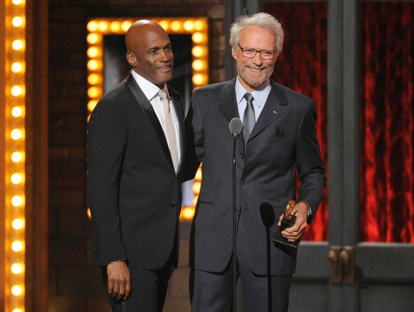 "Clint Eastwood, right, presents the award for best direction in a play to Kenny Leon for ""A Raisin in the Sun"". (Evan Agostini / The Associated Press)"