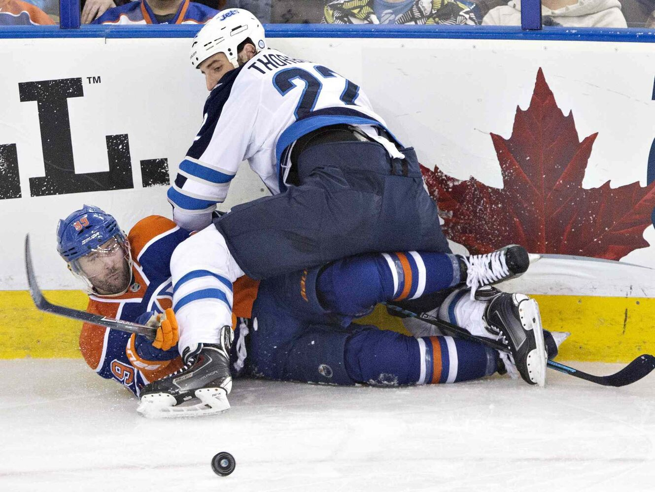 Winnipeg Jets' Eric Tangradi (27) checks Edmonton Oilers' Sam Gagner (89) during the second period on Monday.