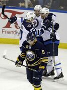 The Sabres' Chad Ruhwedel skates away as Winnipeg Jets forward Aaron Gagnon (top) celebrates his goal with Antti Miettinen (left) and Derek Meech during the second period Monday night in Buffalo.
