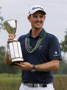 Justin Rose, of England, holds the trophy after winning the Zurich Classic PGA golf tournament, Sunday, April 26, 2015, in Avondale, La. (AP Photo/Butch Dill)