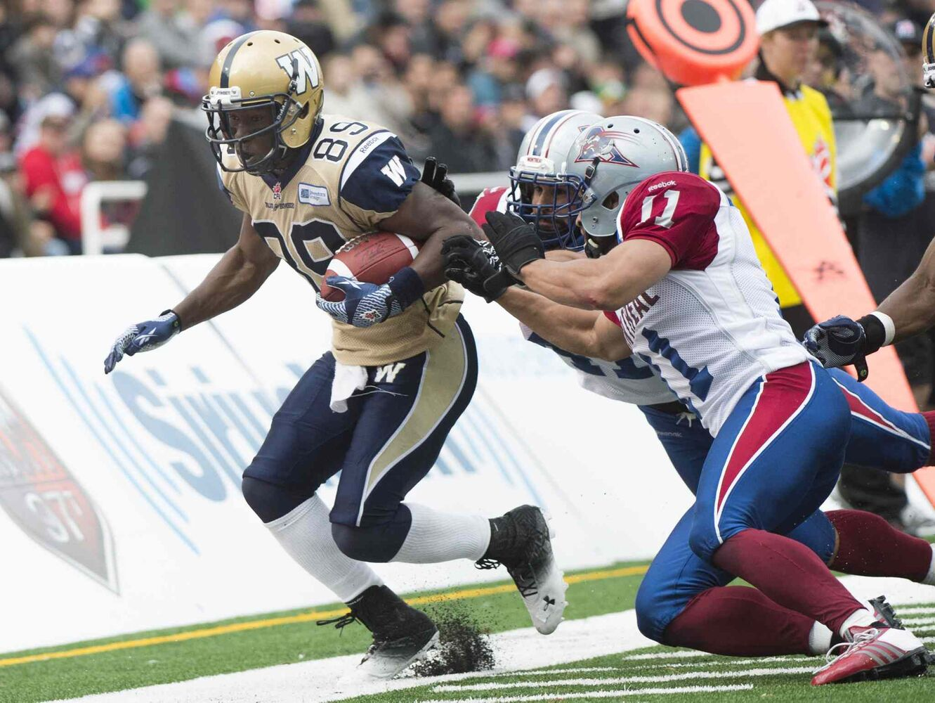 Winnipeg Blue Bombers' Clarence Denmark, left, is tackled by Montreal Alouettes' Chip Cox (11) and Shea Emry during second half CFL football action in Montreal Monday. (Graham Hughes / The Canadian Press)