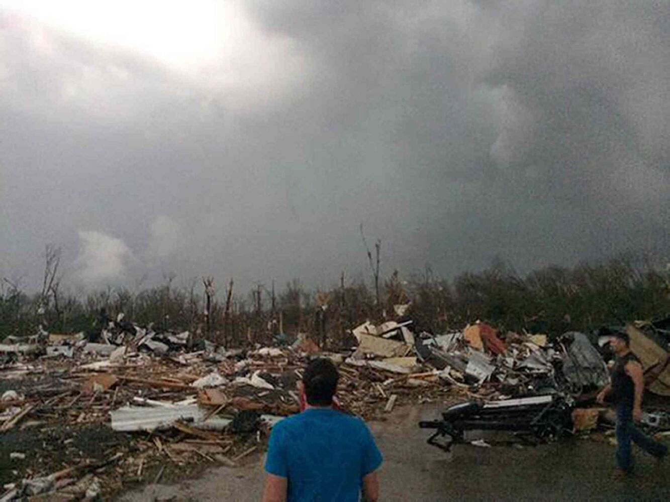 A man surveys the scene following a tornado touchdown in Mayflower, Ark., Sunday. A powerful storm system rumbled through the central and southern United States on Sunday, spawning several tornadoes, including one in a small northeastern Oklahoma city and another that carved a path of destruction through several northern suburbs of Little Rock, Ark.