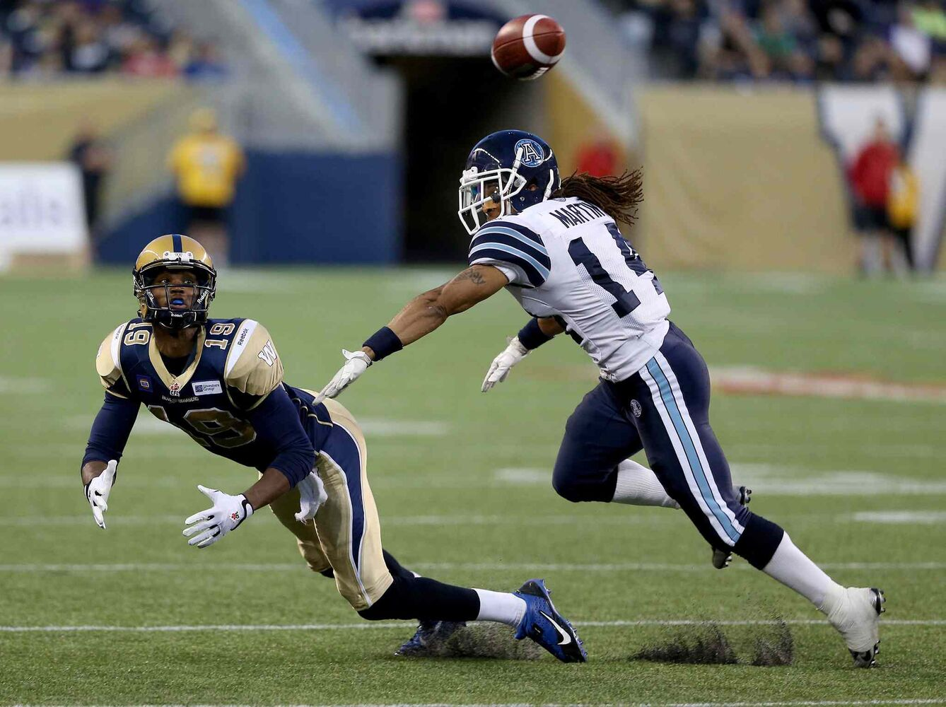 Bombers receiver Aaron Kelly dives for a pass behind Toronto's Andre Martin during the second half. (TREVOR HAGAN / THE CANADIAN PRESS)