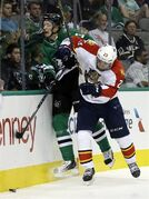 Dallas Stars' John Klingberg (3) of Sweden and Florida Panthers' Rocco Grimaldi (23) slam against the boards trying to reach a loose puck in the second period of a preseason NHL hockey game, Monday, Sept. 29, 2014, in Dallas. (AP Photo/Tony Gutierrez)