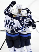 Winnipeg Jets' Tobias Enstrom, bottom right, of Sweden, is hugged by teammates after scoring the go-ahead goal against the San Jose Sharks during the third period of an NHL hockey game on Thursday, March 27, 2014, in San Jose, Calif. The Jets won 4-3.