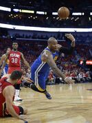 Golden State Warriors' Marreese Speights tries to dish off the ball as he falls to the court with New Orleans Pelicans forward Ryan Anderson, lower left, during the first half of Game 3 of a first-round NBA basketball playoff series in New Orleans, Thursday, April 23, 2015. (AP Photo/Gerald Herbert)