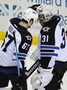 Winnipeg Jets' right winger Michael Frolik (67) and Ondrej Pavelec (34) celebrate a win over the Buffalo Sabres Wednesday in Buffalo, N.Y.  Winnipeg won 2-1.