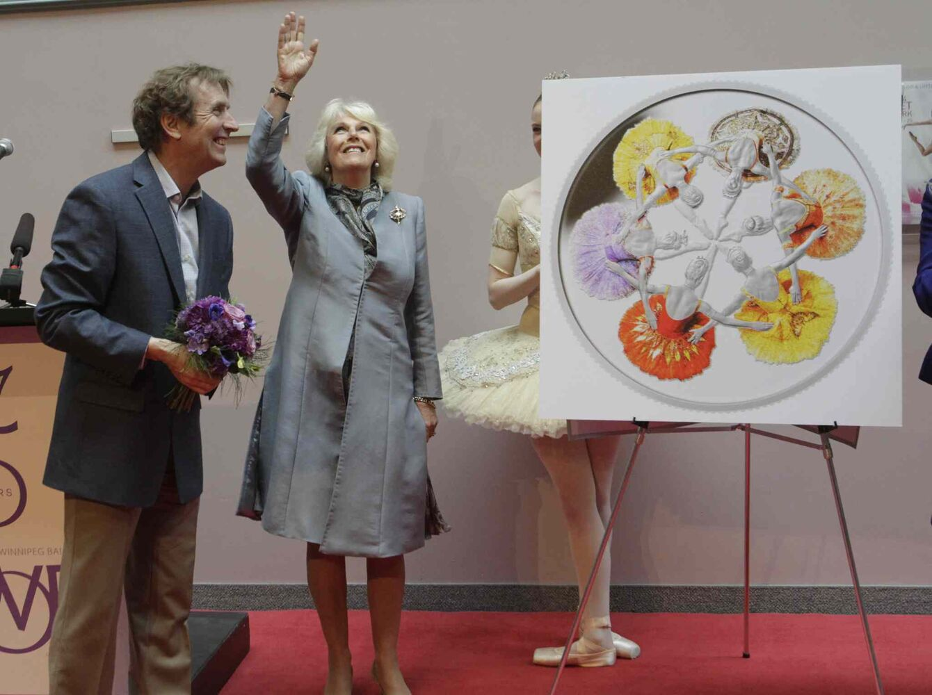 Camilla, Duchess of Cornwall with RWB Artistic Director Andre Lewis during Canada's Royal Winnipeg Ballet building visit. At right is the new silver collector coin to commemorate the 75th anniversary of Canada's Royal Winnipeg Ballet.