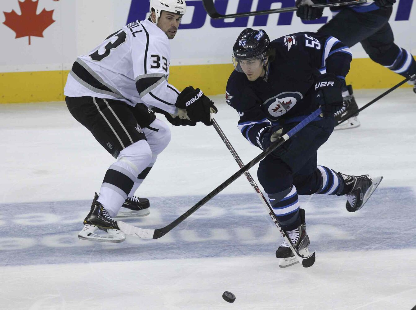 Winnipeg Jets' Mark Scheifele (55) stickhandles around Los Angeles Kings' Willie Mitchell (33) in the second period. (MIKE DEAL / WINNIPEG FREE PRESS)