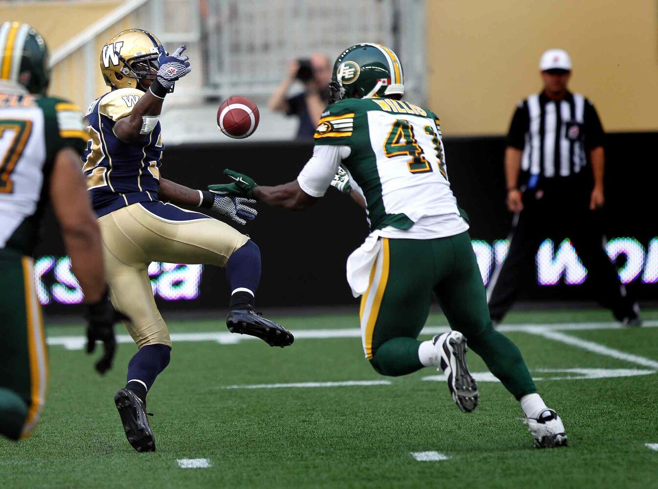 Winnipeg Blue Bombers' running back Nic Grigsby bobbles a pass into the waiting hands of Edmonton Eskimos' Odell Willis early in the game Thursday. Willis took it and ran to score the Eskimo's opening touch down.  (Phil Hossack / Winnipeg Free Press)