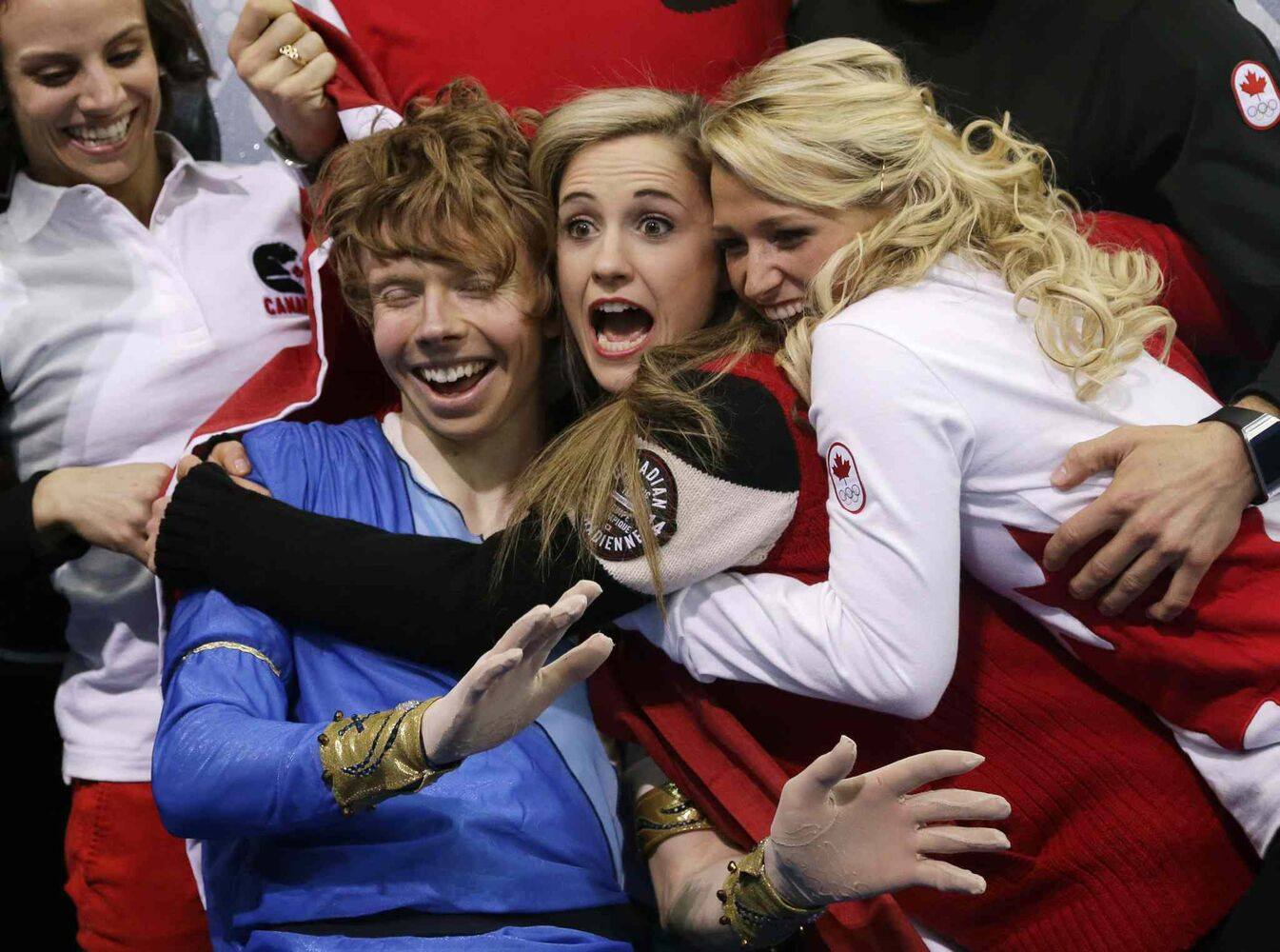 Kevin Reynolds of Canada (left) reacts with teammates after competing in the men's team free skate figure skating competition at the Iceberg Skating Palace during the 2014 Winter Olympics. (Darron Cummings / The Associated Press)