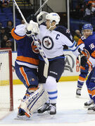 Islanders goalie Kevin Poulin gets into it with  Winnipeg captain Andrew Ladd.