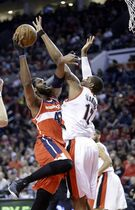 Washington Wizards center Nene, left, shoots against Portland Trail Blazers forward LaMarcus Aldridge during the first half of an NBA basketball game in Portland, Ore., Saturday, Jan. 24, 2015. (AP Photo/Don Ryan)