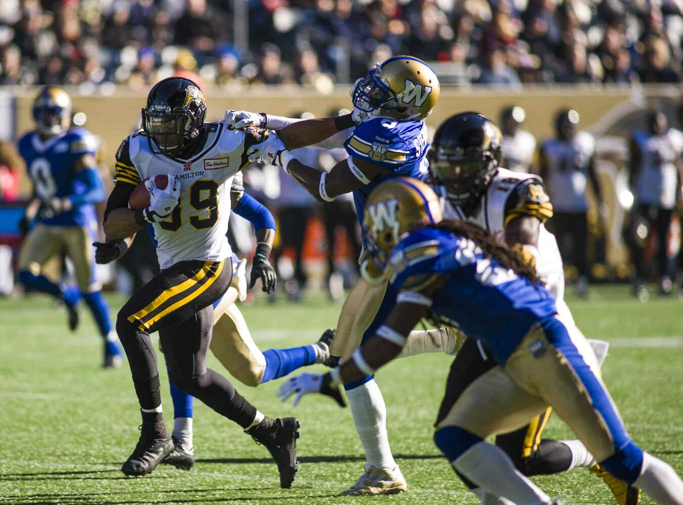 The Winnipeg Blue Bombers Brandon Stewart (8) attempts to take down Hamilton Tiger-Cats Onrea Jones (89) Saturday afternoon at Investors Group Field.