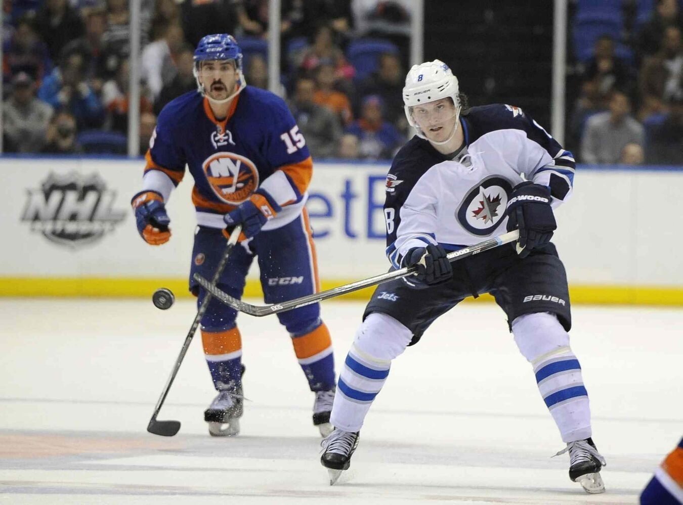 Winnipeg Jets defenceman Jacob Trouba (right) flicks the puck down the ice and away from New York Islanders forward Cal Clutterbuck in the third period. (Kathy Kmonicek / The Associated Press)