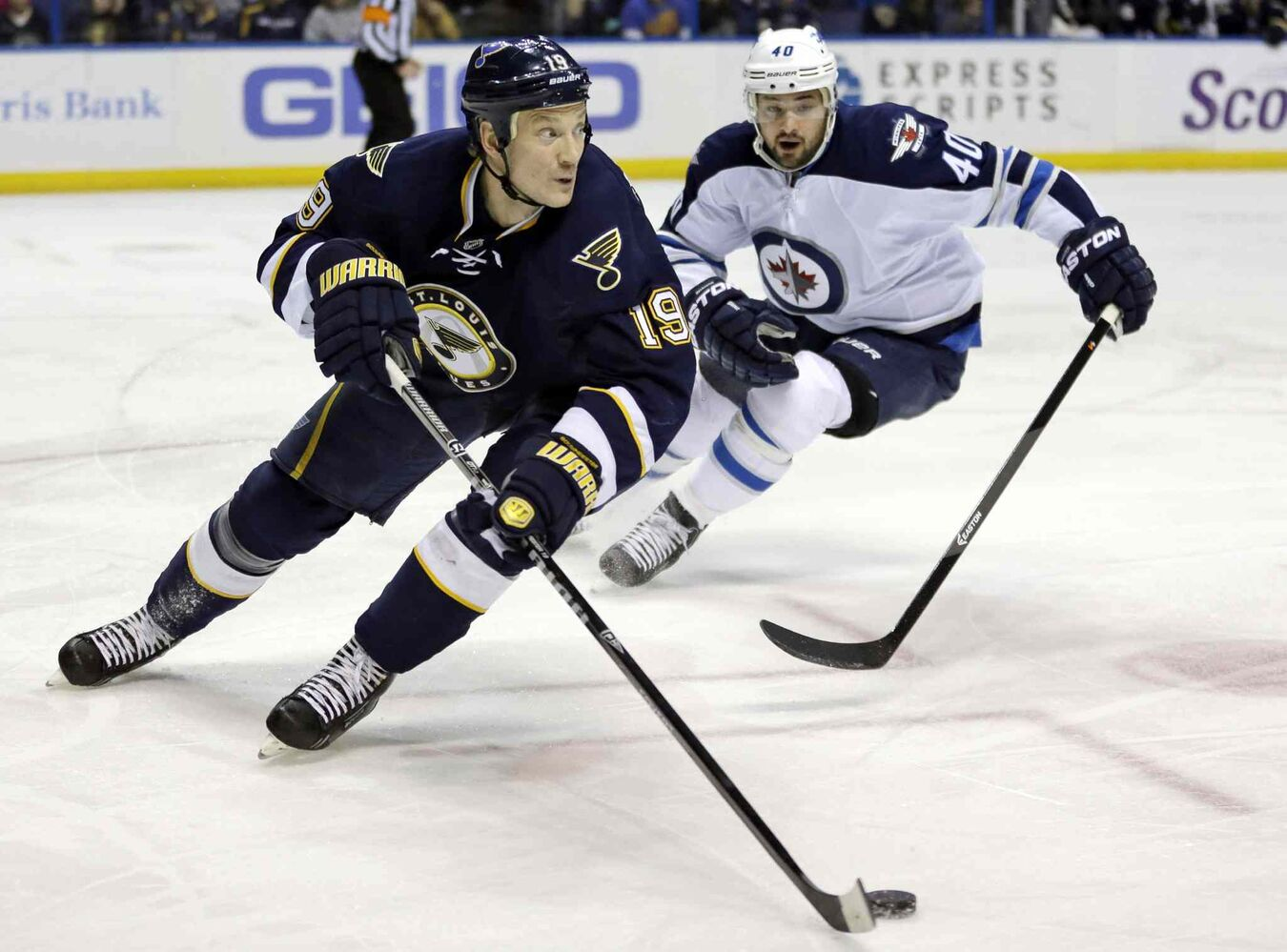 St. Louis Blues' Jay Bouwmeester, left, controls the puck as Winnipeg Jets' Devin Setoguchi gives chase during the first period of Saturday's game. (Jeff Roberson / The Associated Press)