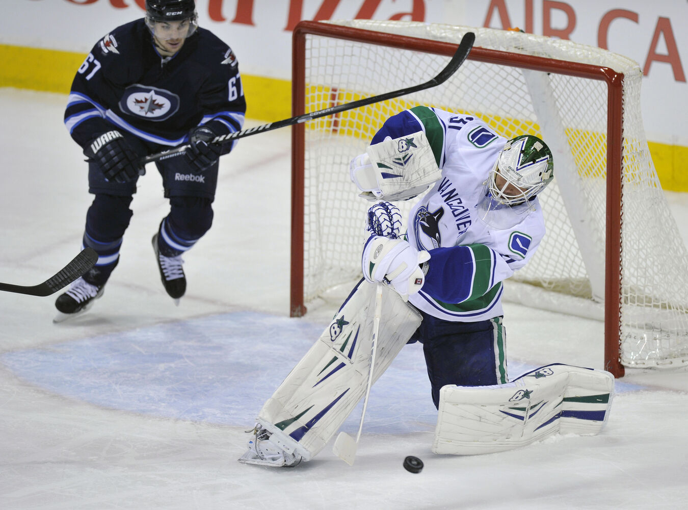 Winnipeg Jets' Michael Frolik runs at the net as Vancouver Canucks' goaltender Eddie Lack  clears the puck during the first period of Friday's game. (Fred Greenslade / Special for the Winnipeg Free Press)