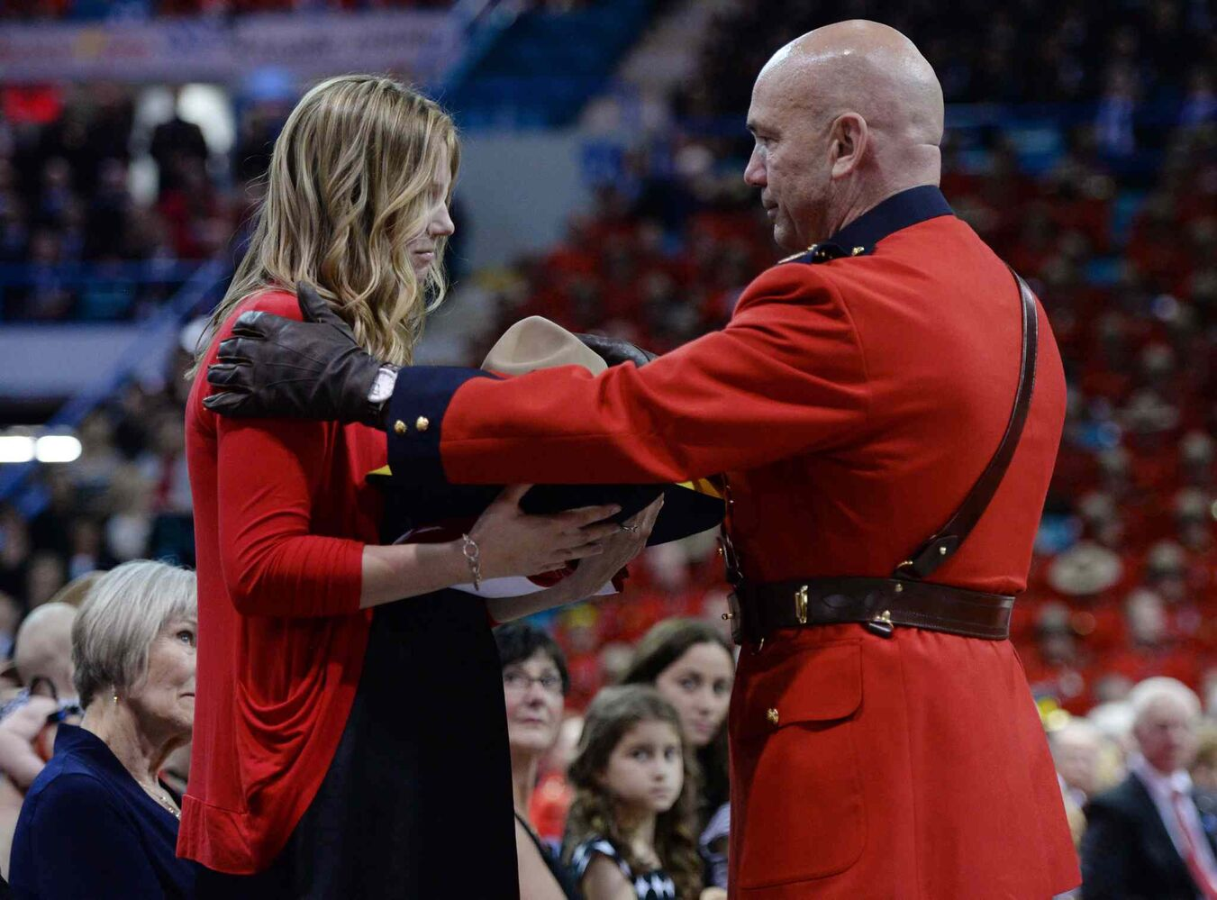 RCMP Commissioner Bob Paulson (right) presents Const. Dave Ross's widow Rachael with the slain RCMP officer's Stetson at a regimental funeral for the three slain officers. (Sean Kilpatrick / The Canadian Press)