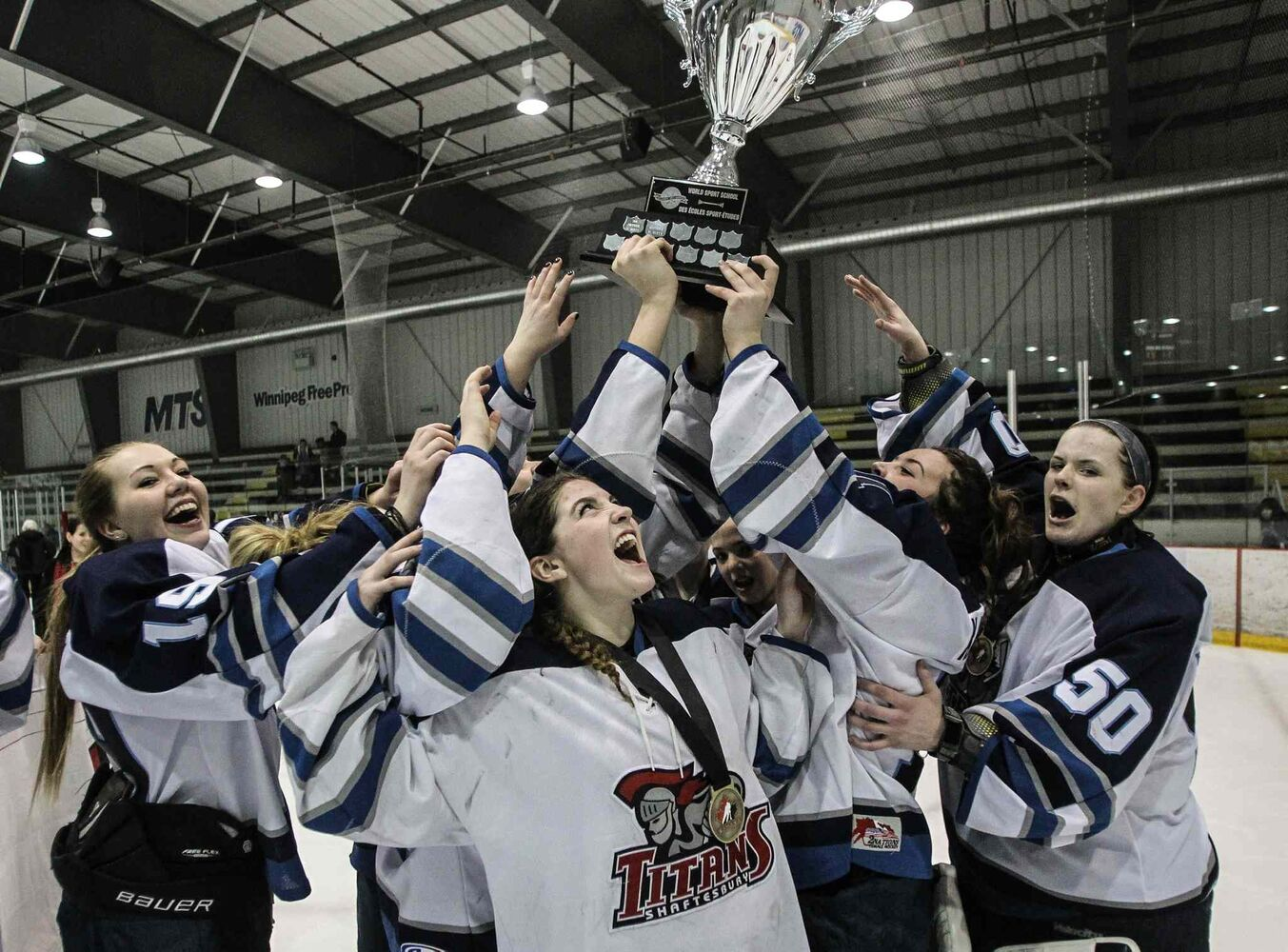 Justine Fredette (centre) cheers as her Shaftesbury Hockey Academy Titans teammates hoist the trophy after defeating the Kelowna, B.C.-based Pursuit of Excellence Hockey Academy 5-2 in the gold-medal game at the Female World Sport School Challenge Sunday at MTS Iceplex. Fredette scored a hat trick to lead her team to victory.