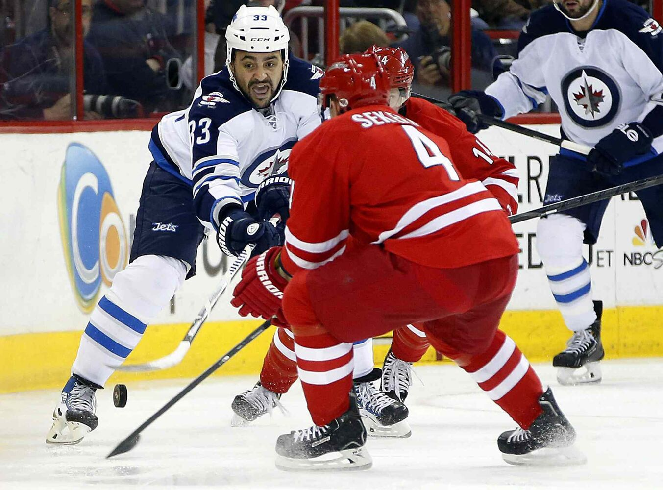 Winnipeg Jets' Dustin Byfuglien (33) tries to clear the puck past Carolina Hurricanes' Andrej Sekera (4) in the first period of Tuesday's hockey game.