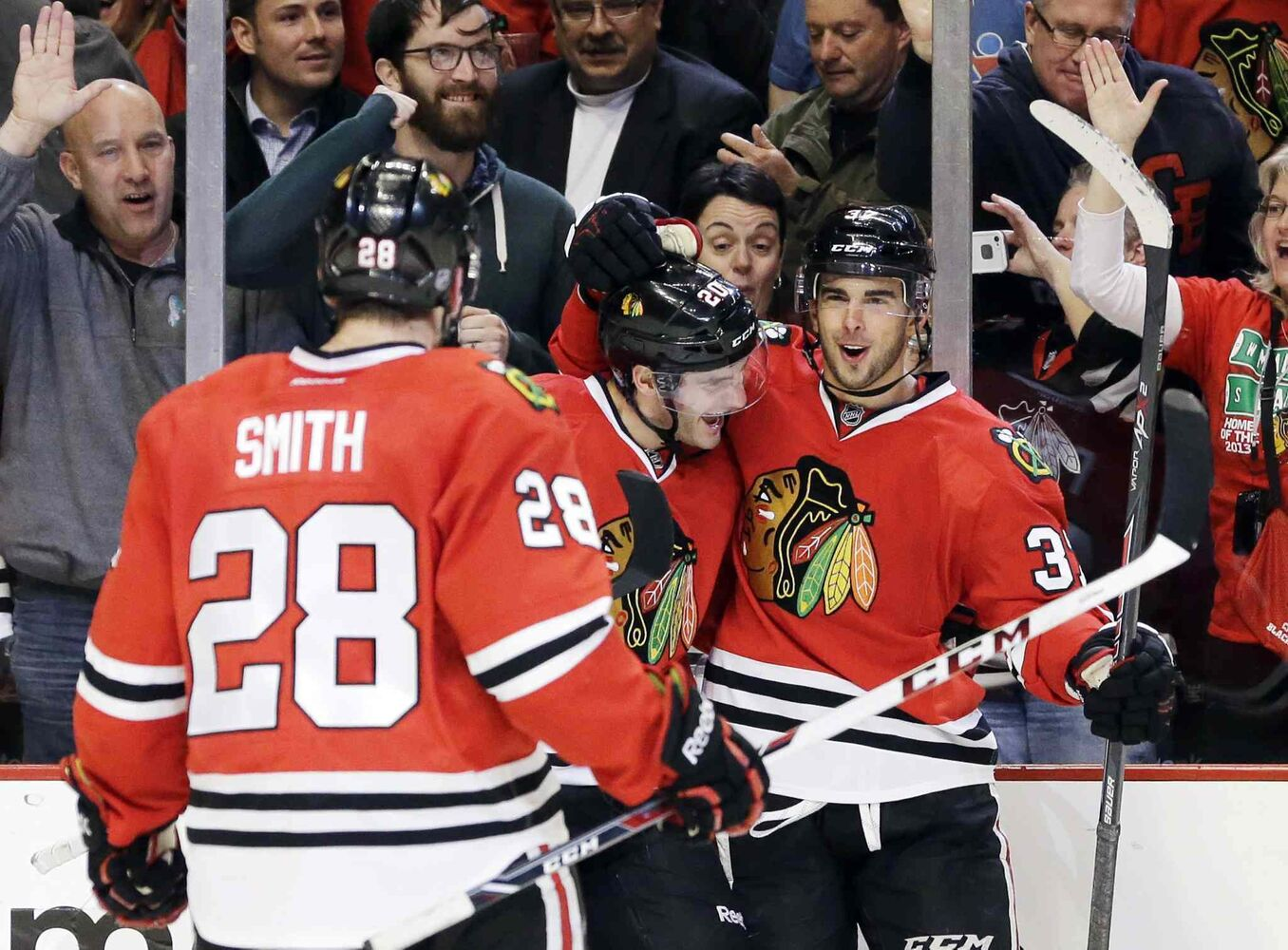 Chicago Blackhawks' Brandon Pirri (right) celebrates with Brandon Saad (centre) and Ben Smith (28) after Pirri scored a goal during the second period. (Nam Y. Huh / The Associated Press)