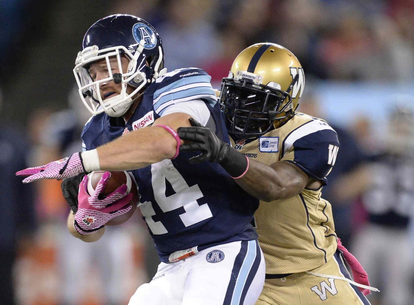 Toronto Argonauts' Chad Kackert runs the ball as a Winnipeg Blue Bombers player defends during the first quarter.