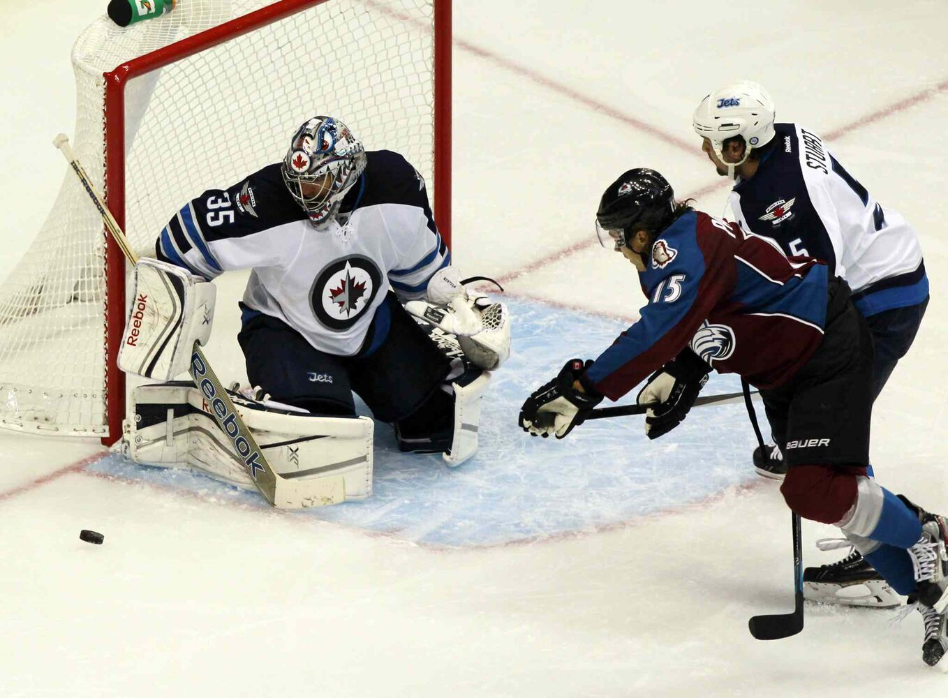 Winnipeg Jets goalie Al Montoya makes a stick save off a shot by Colorado Avalanche winger PA Parenteau (centre) as Jets defenceman Mark Stuart backchecks during the third period. (David Zalubowski / The Associated Press)