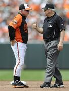 FILE - In this June 8, 2014, file photo, Baltimore Orioles manager Buck Showalter, left, talks with second base umpire Larry Vanover before a review of a hit by Oakland Athletic's John Jaso in the third inning of a baseball game in Baltimore. The call was overturned from a grand slam to a two run double. (AP Photo/Gail Burton, File)