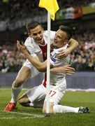 Poland's Slawomir Peszko, right, celebrates with Pawel Olkowski after scoring a goal against Republic of Ireland during their Euro 2016 Group D qualifying soccer match at the Aviva stadium, Dublin, Ireland, Sunday, March 29, 2015. (AP Photo/Peter Morrison)